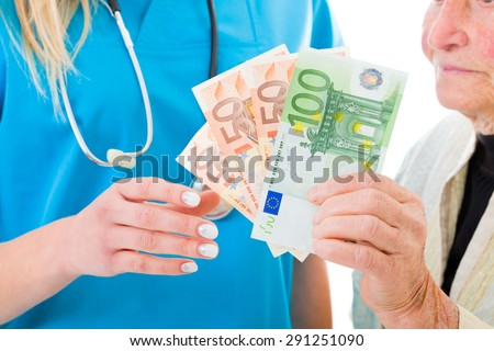 Senior woman giving soap money to doctor - healthcare costs concept. - stock photo
