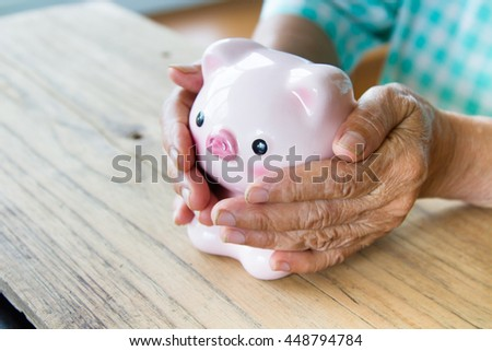 Senior woman hand covering piggy bank, metaphoric for hope, saving, retirement, pension and life insurance. - stock photo