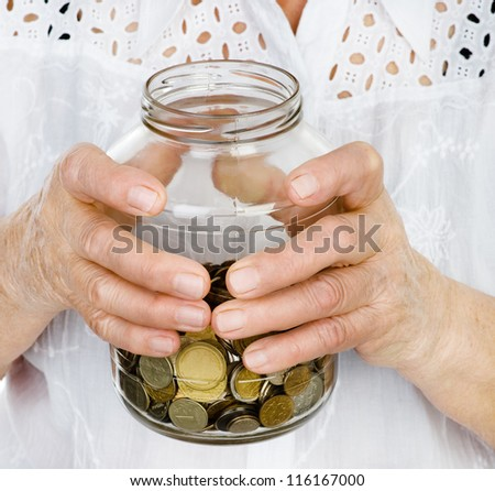 Senior woman hands holding jar with coins closeup. isolated on white background - stock photo