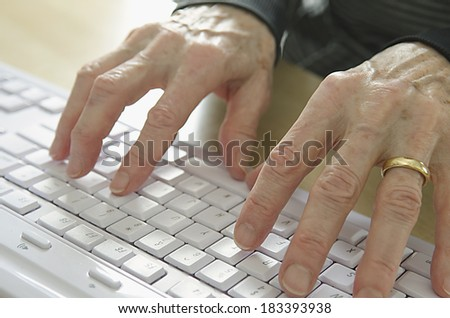 senior woman hands on computer keyboard - stock photo