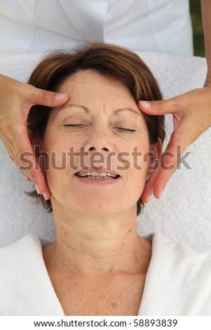 Senior woman having a face massage - stock photo