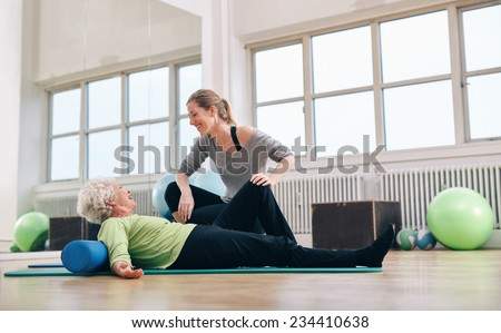 Senior woman having a friendly chat with her personal trainer while exercising at gym. Elder woman doing pilates with gym coach.