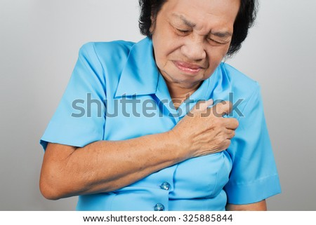 Senior woman having a heart attack and grabbing her chest - stock photo