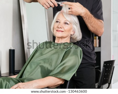 Senior woman having hair cut at beauty salon - stock photo