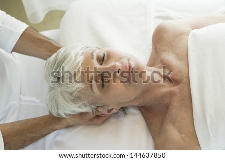Senior woman having head massage - stock photo