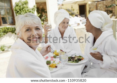 Senior woman having healthy food with friends in the resort - stock photo