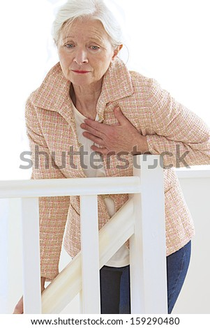 senior woman having heart attack in her stairs - stock photo