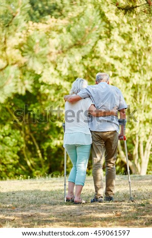 Senior woman helping man on crutches in the park in summer