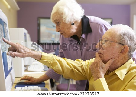 Senior woman helping senior man use computer