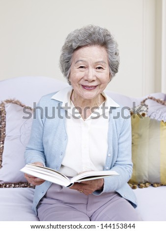senior woman holding a book and smiling. - stock photo