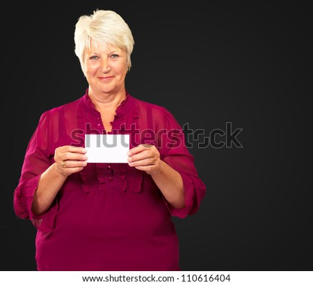 Senior Woman Holding A Card On Black Background