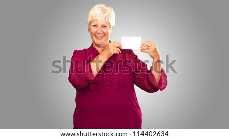 Senior Woman Holding A Card On gray Background