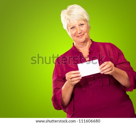 Senior Woman Holding A Card On Green Background - stock photo