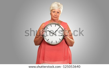Senior Woman Holding A Clock On gray Background