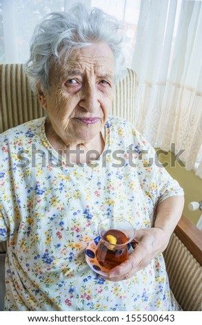 senior woman holding a glass of tea while sitting in armchair at her living room