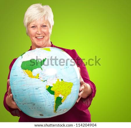 Senior Woman Holding A Globe On Green Background - stock photo