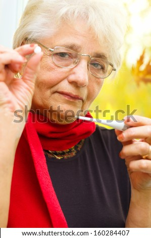 senior woman holding a pill in her hand, preparing to eat that - part of a series.