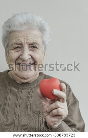 senior woman holding a red heart