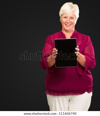 Senior Woman Holding A Touch pad On A Black Background - stock photo