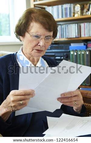 Senior Woman Holding Bills and Looking Worried - stock photo