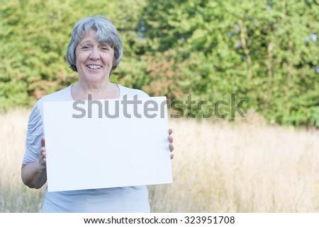 Senior woman holding blank sign - stock photo