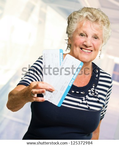 Senior Woman Holding Boarding Pass, Indoors - stock photo