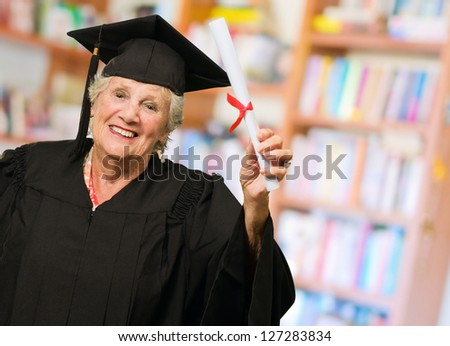 Senior Woman Holding Graduation Certificate, Indoors - stock photo