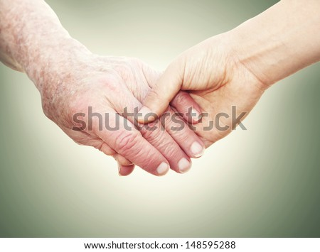 Senior Woman Holding Hands with a Young Lady on a green vintage background - stock photo
