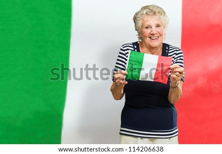 Senior Woman Holding Italy Flag And Standing Against Flag - stock photo