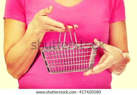 Senior woman holding mini shopping basket