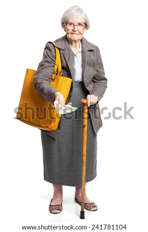 Senior woman holding money while standing over white background  - stock photo