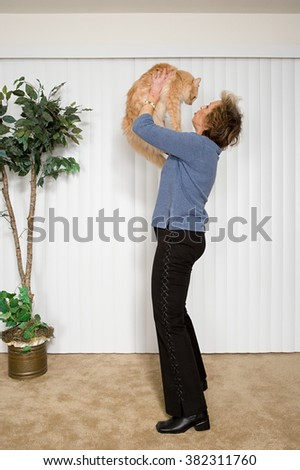 Senior woman holding pet cat - stock photo