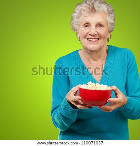 Senior woman holding popcorn isolated on green background