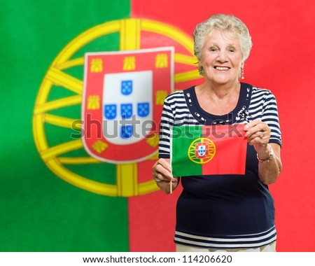 Senior Woman Holding Portugal Flag And Standing Against Flag - stock photo
