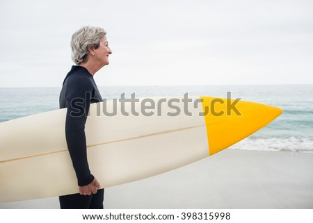 Senior woman holding surfboard on the beach on a sunny day - stock photo