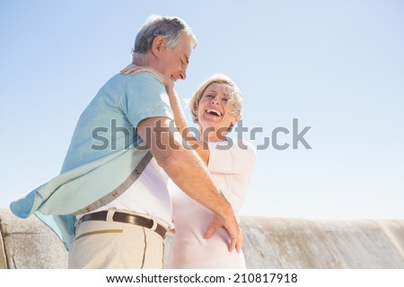 Senior woman hugging her partner on a sunny day - stock photo