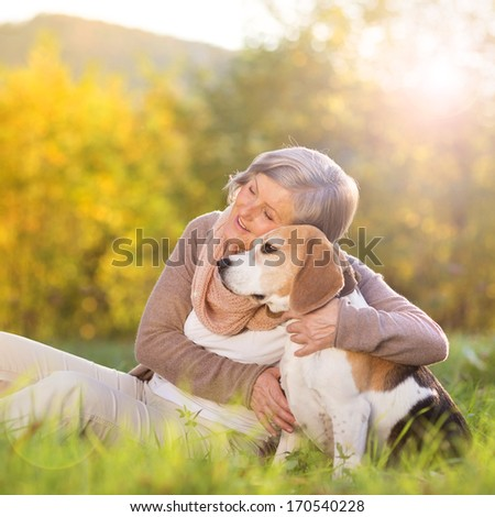 Senior woman hugs her beagle dog in countryside - stock photo