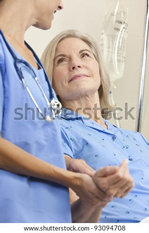 Senior woman in a hospital bed having her pulse taken by a female doctor with stethoscope - stock photo