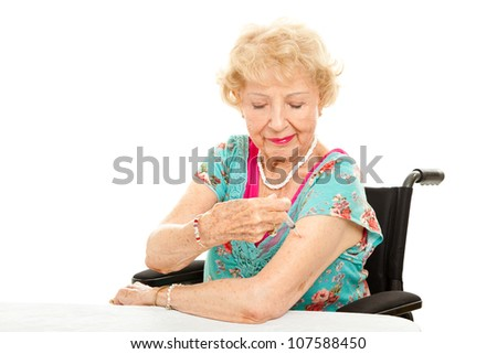 Senior woman in a wheelchair, giving herself an injection.  White background. - stock photo