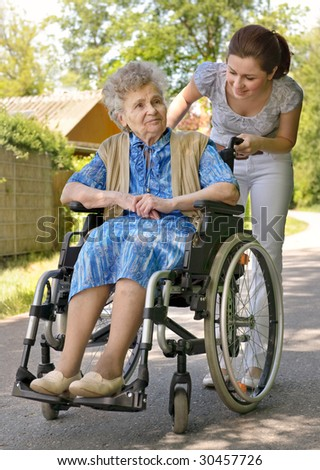 Senior woman in a wheelchair with her granddaughter - stock photo