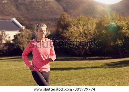 Senior woman in atheltic wear enjoying a morning jog outdoors, with grass and trees around her and gentle sunflare