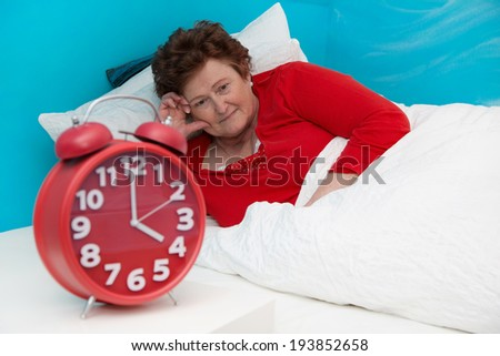 Senior woman in bed ill and suffered of sleeplessness or insomnia. - stock photo