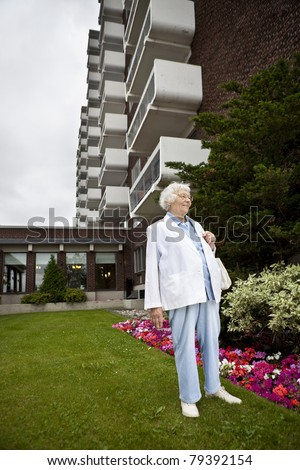 Senior woman in front of apartment building - stock photo