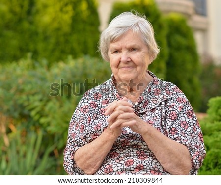 Senior  woman  in garden.  MANY OTHER PHOTOS FROM THIS SERIES IN MY PORTFOLIO. - stock photo