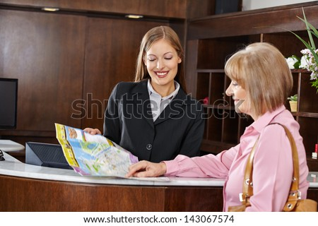 Senior woman in hotel looking at city map with female receptionist - stock photo