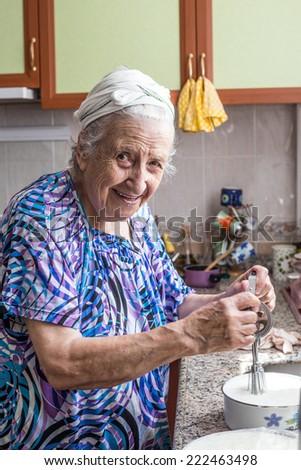senior woman in kitchen - stock photo