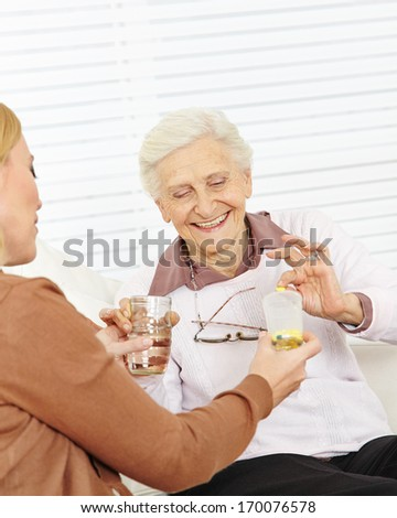 Senior woman in nursing home taking medical pills with water - stock photo