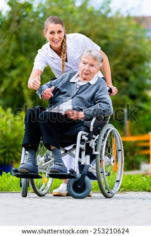 Senior woman in nursing home with nurse in garden sitting in wheelchair giving the thumbs up sign - stock photo