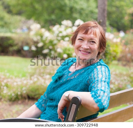 Senior woman   in  park with blooming roses - stock photo