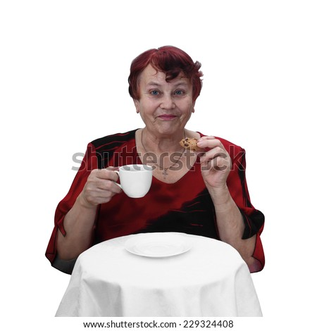 Senior woman in red dress sits behind table with coffee cup and cookie in hands. Portrait isolated on white background